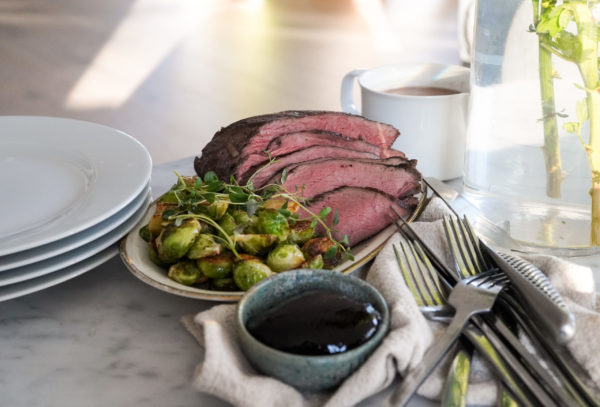 Ett serveringsfat med helstekt kött och brysselkål redo för dukning tillsammans med bland annat tallrikar och bestick