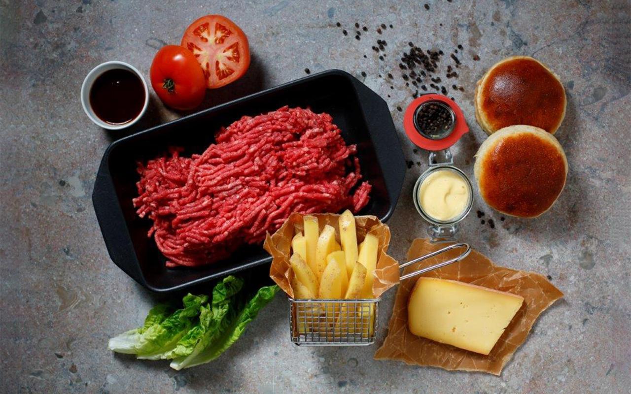 Hamburgarekött, bröd, tomater, ost, sås, och pommes