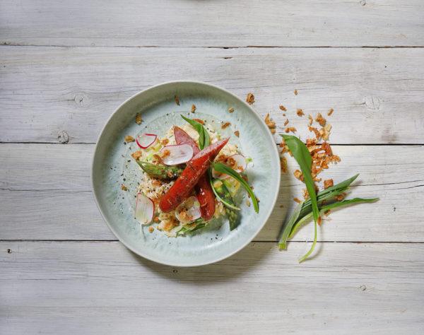 En tallrik med risoni och lammkorv med gröna och röda tillbehör
