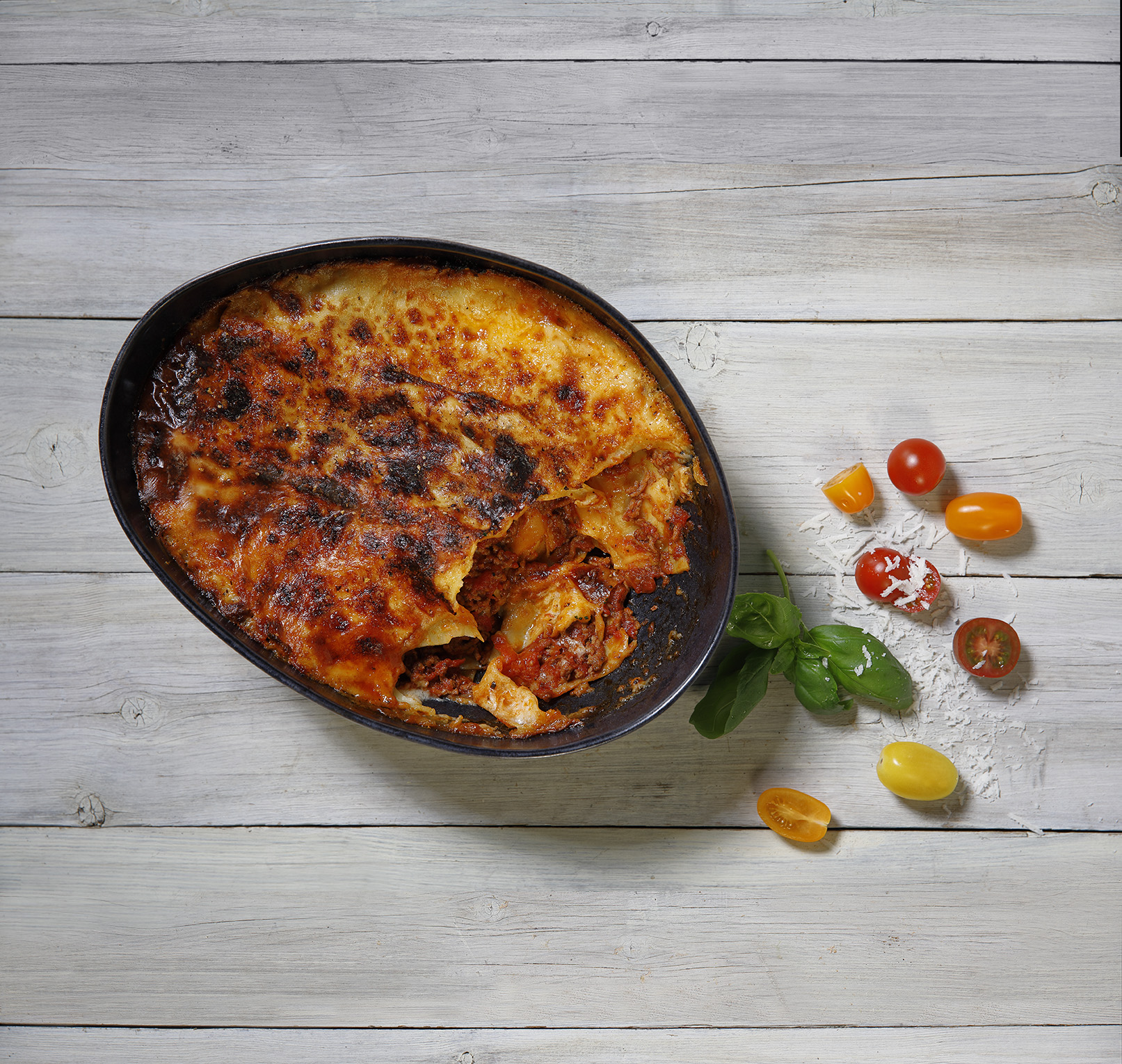 En form lasange dekorerad med körsbärstomater, basilika och parmesan