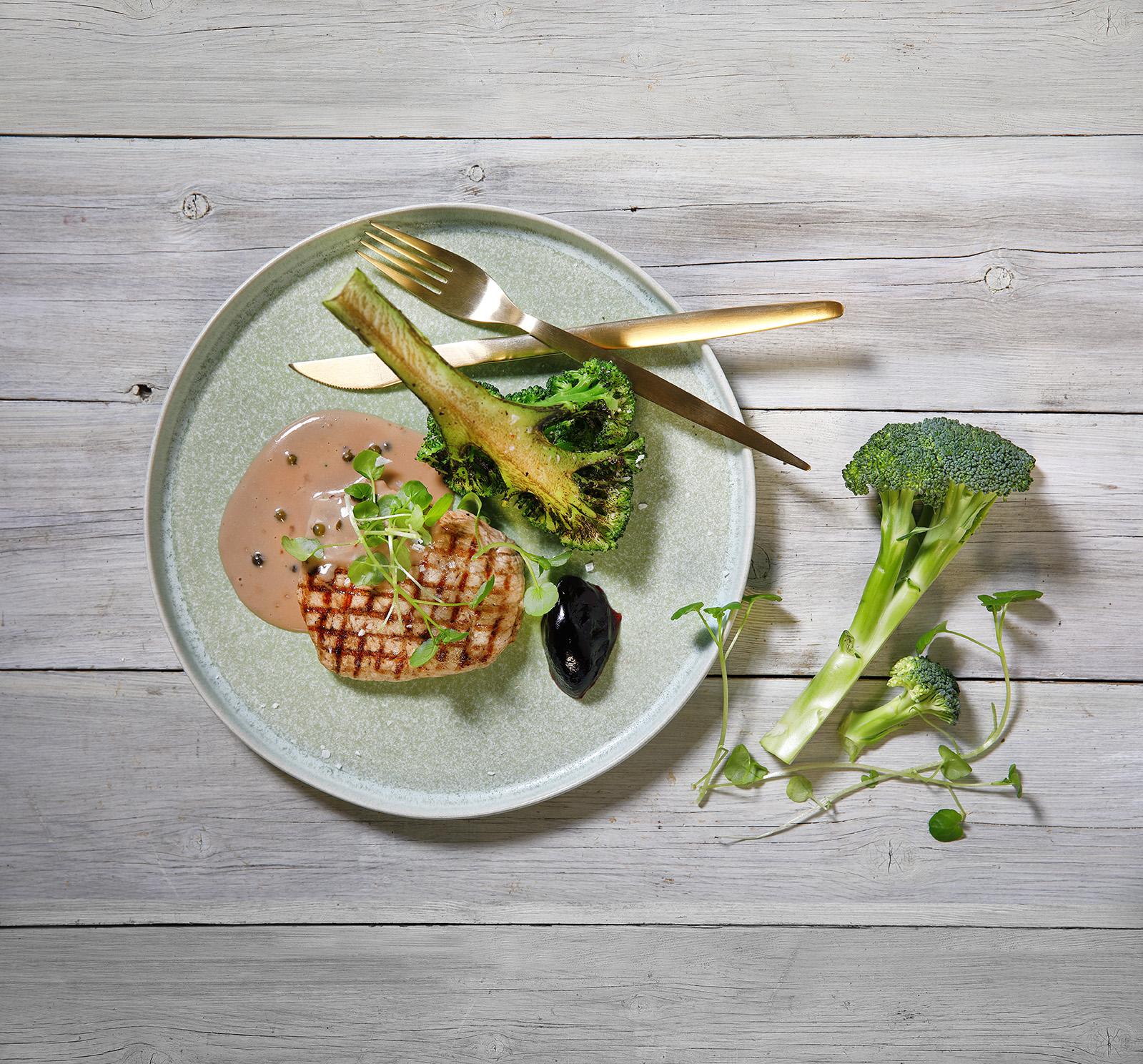 En tallrik med grillat kött, brocolli och en pepprig sås