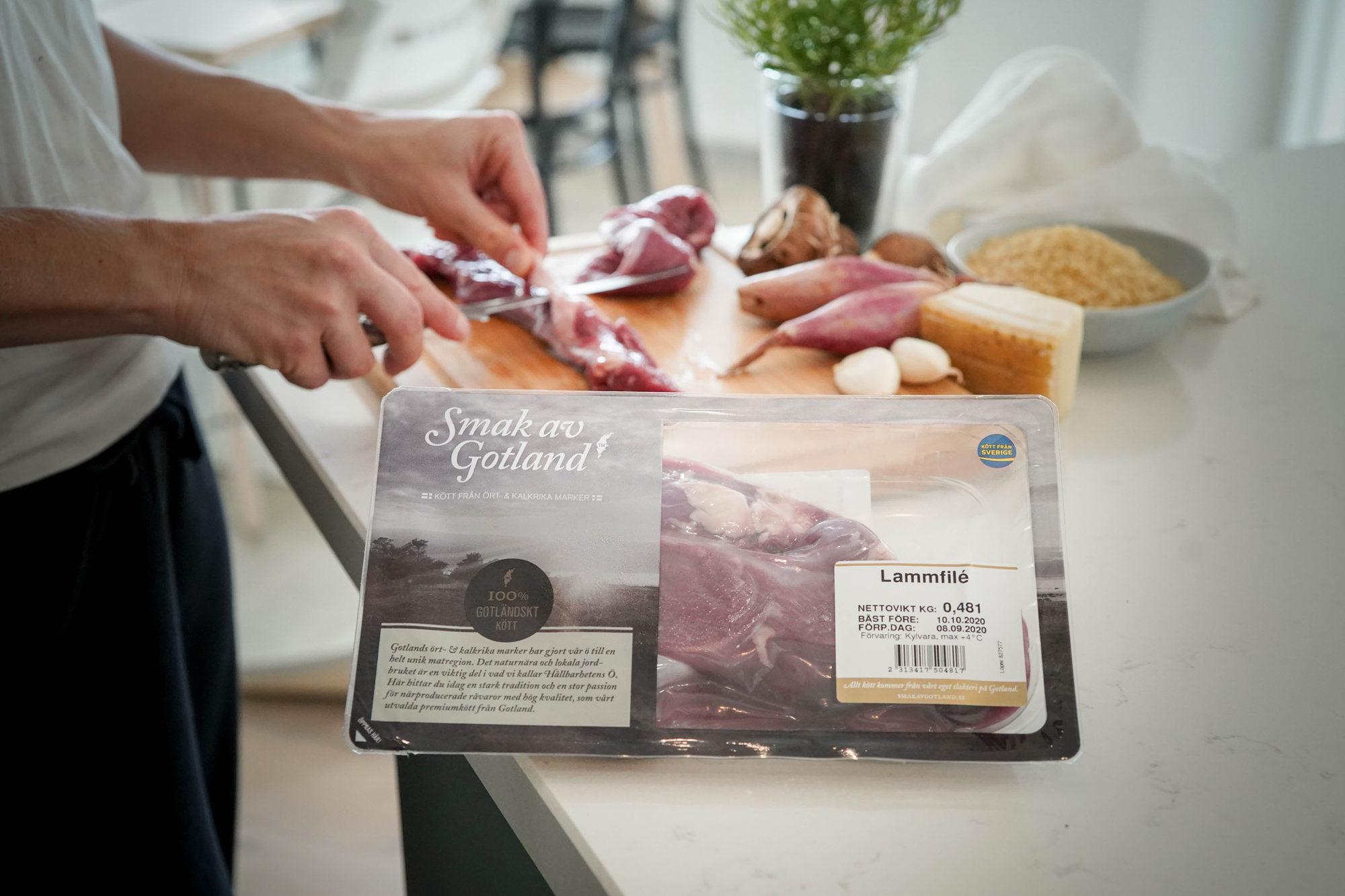 Person som skär lammfilén i bakgrunden av förpackningen samt förbereder tillbehör